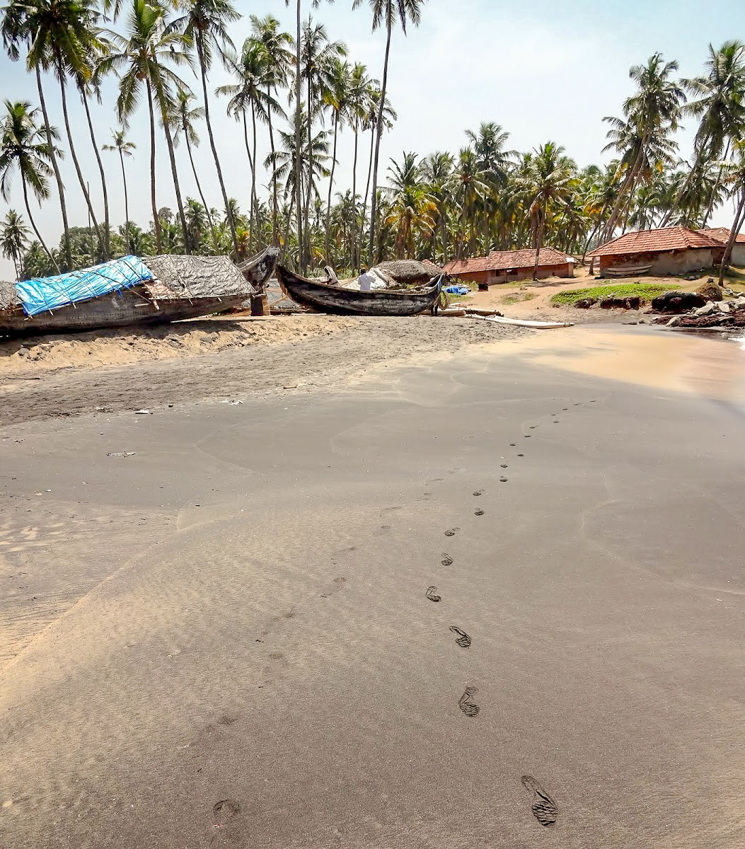 Footprints in the sand on Odayam beach, in the background wooden boats and palm trees, Varkala, Kerala, India