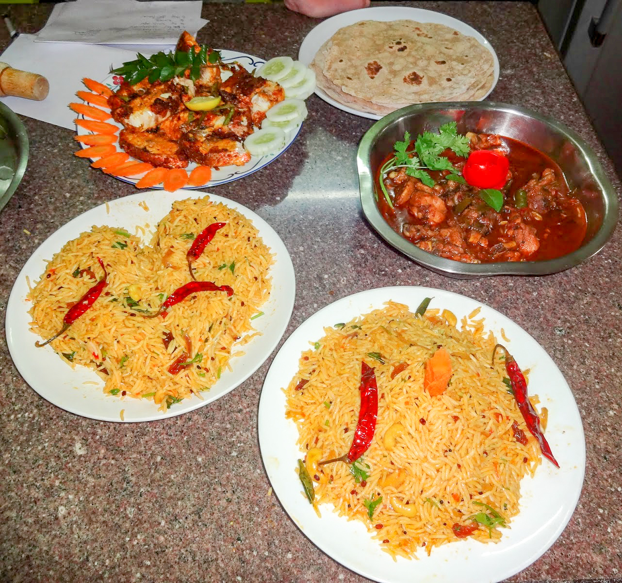 2 plates of cashew and red chilli rice, a plate of chicken chunks surrounded by carrot and cucumber slices, chicken curry in a dish with corriander leaves and a plate of chapati at Khan's Cooking Class, Varkala, India