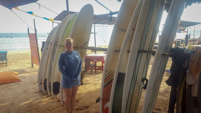 Rosie wearing a blue wet-shirt stands in front of surfboards on the beach in Sri Lanka