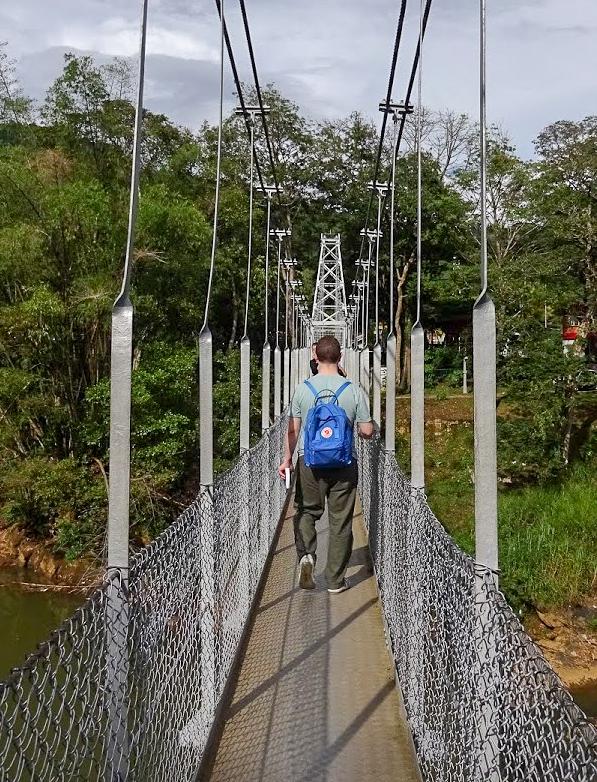 Karl walking across a metal bridge in the Royal Botanical Gardens, Peradeniya, Sri Lanka