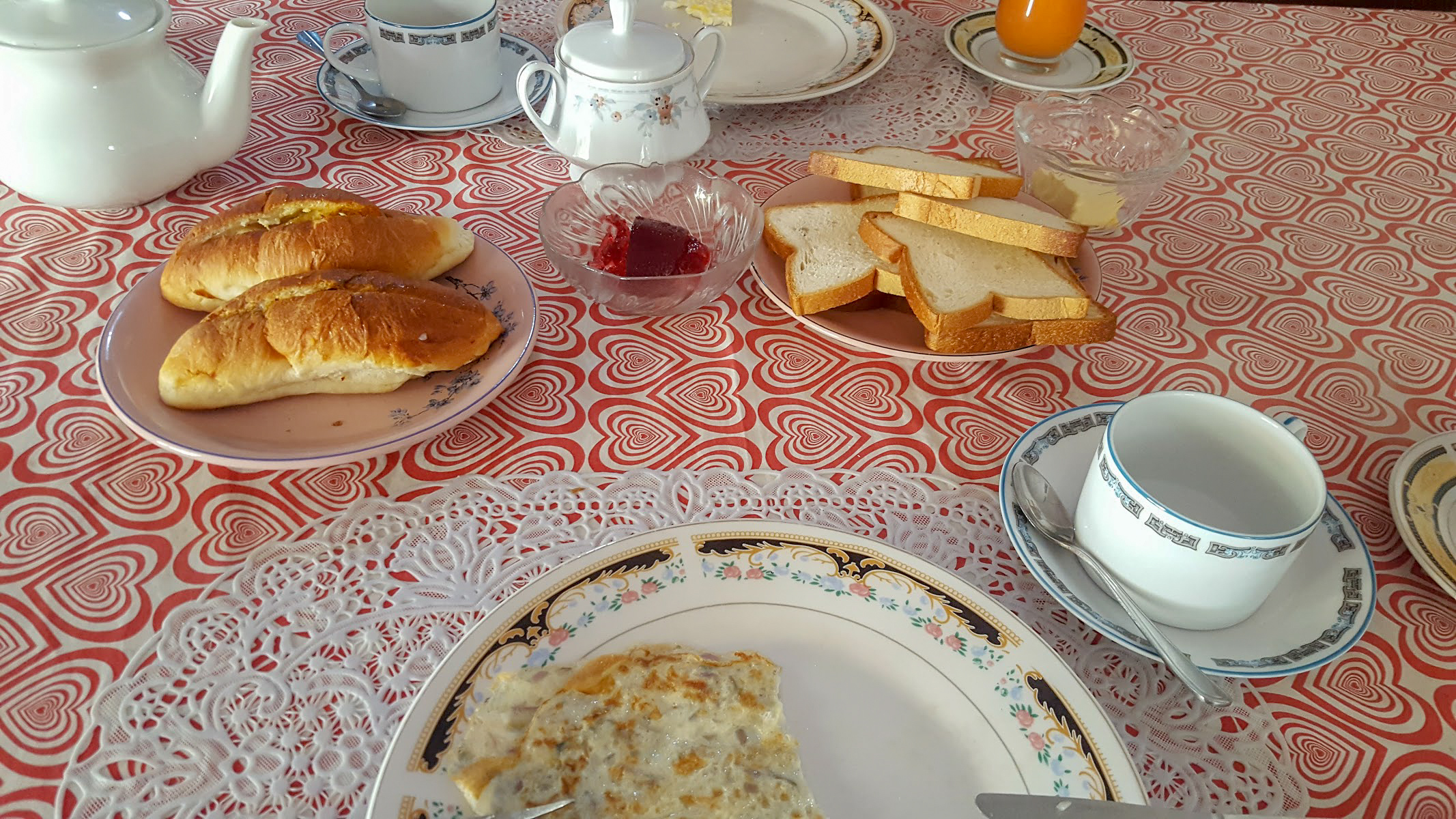 breakfast of toast, omlette and rolls on a red love heart tablecloth