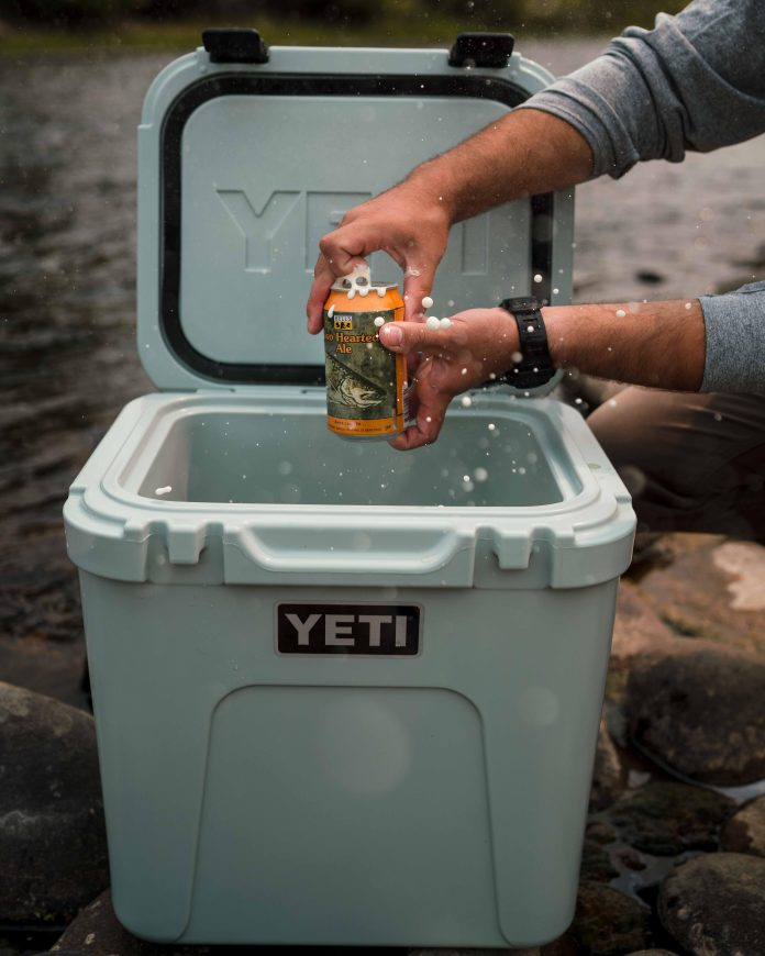 cracking a beer over the cooler