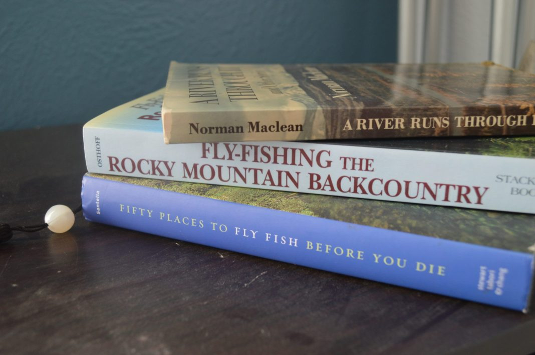 A stack of fly fishing books on a wooden table