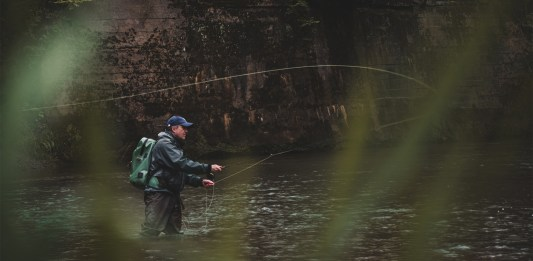 An angler casting through the blades of grass