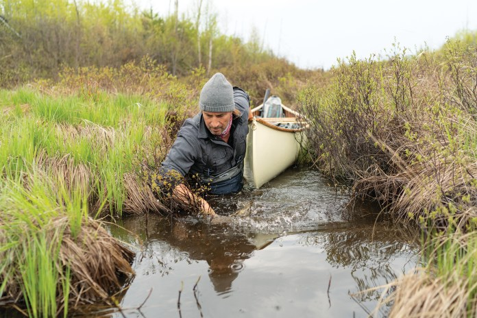 Boots in the water and paddle on the bow seat, Nathaniel Riverhorse Nakadate navigates a tight, soggy portage.