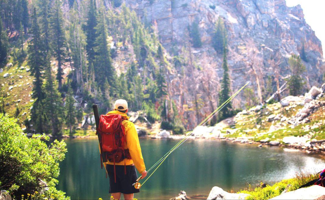 Angler standing beside an alpine lake in Grand Teton National Park
