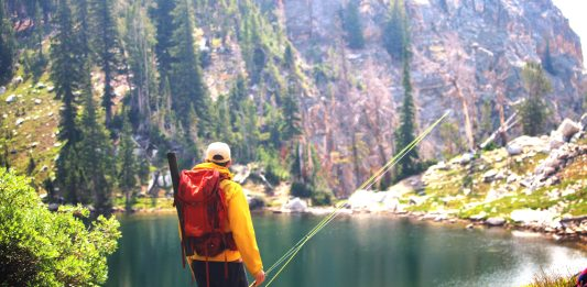 Angler standing beside an alpine lake in Grand Teton National Park
