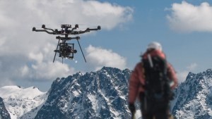 drone flying in snowy mountain range