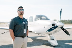 Flight school teacher in from of Cessna airplane