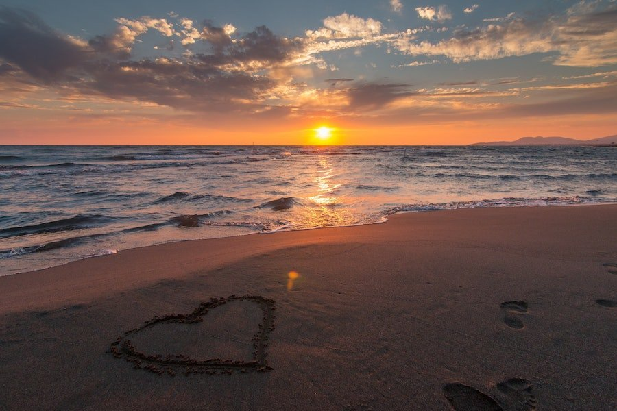 Beach sunset over the ocean in Bali with a heart drawn in the sand
