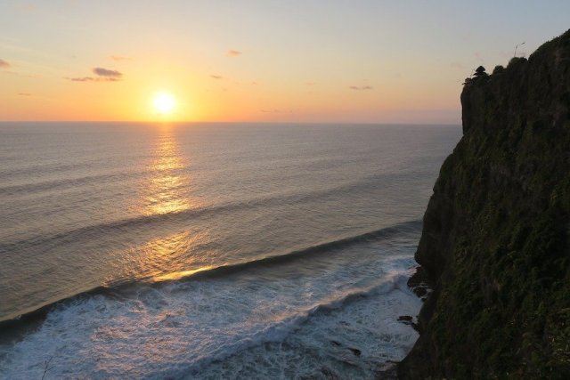 Sunset over the ocean in Bali with Uluwatu temple in foreground
