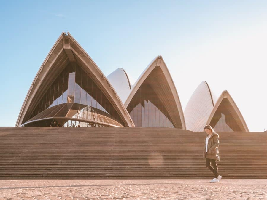 Woman walking in front of Sydney Opera House