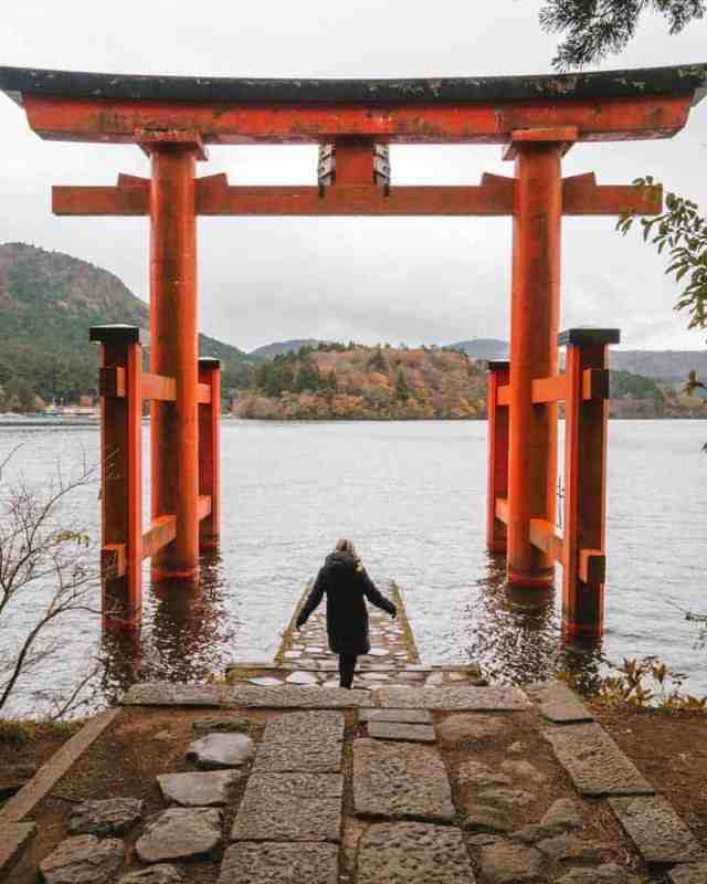 Woman walking through Japanese gate overlooking lake