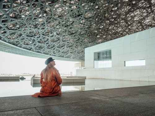 Central pool at the Louvre Abu Dhabi under the helix dome roof with girl wearing orange jacket