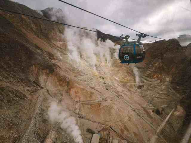 Sulphur gases rising from Mount Hakone volcanic area of Owakudani and the Hakone Ropeway cable car passing overhead