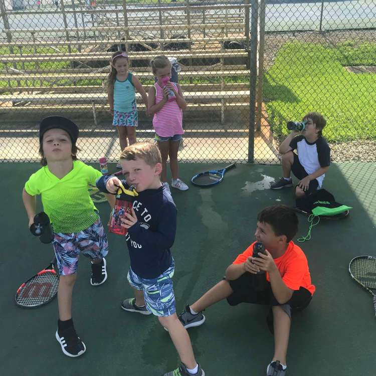 Children enjoying youth summer tennis camp