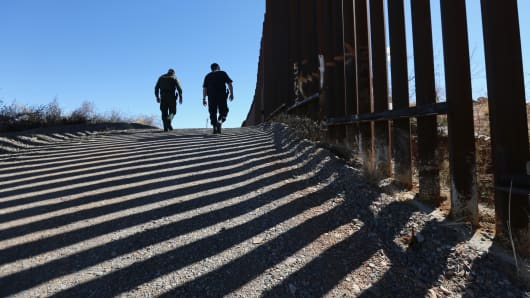 U.S. Customs and Border Protection personnel walk along a section of fence at the U.S.-Mexico border.