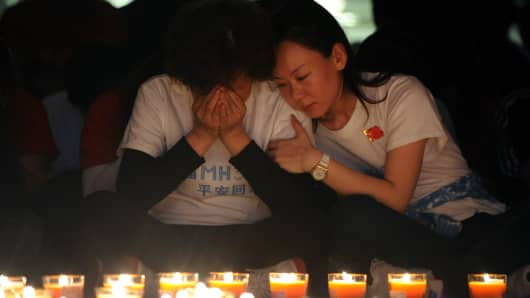 Chinese relatives of passengers on the missing Malaysia Airlines flight MH370 pray in front of candles at the Metro Park Hotel in Beijing.