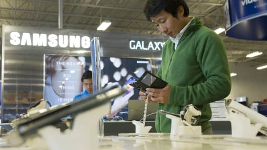 A customer looks at the new Samsung Electronics Co. Galaxy S5 smartphone on display at a Best Buy Co. store in San Francisco, California, U.S..