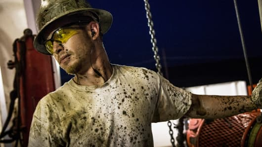 A worker for Raven Drilling, helps line up a pipe while drilling for oil in the Bakken shale formation outside Watford City, North Dakota.