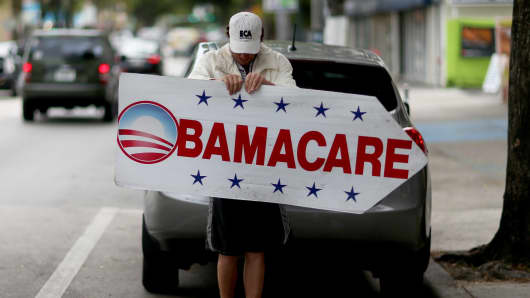A man holds a sign directing people to an insurance company where they can sign up for the Affordable Care Act, in Miami last month.