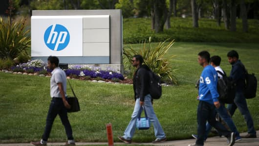 Pedestrians walk by a sign outside of the Hewlett-Packard headquarters in Palo Alto, California.