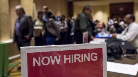 'Now Hiring' signage is displayed as job seekers wait in line to enter the San Jose Career Fair in San Jose, California.