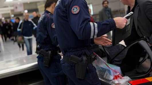French customs officers check luggages at the the Roissy-Charles-de-Gaulle airport on December 3, 2015.