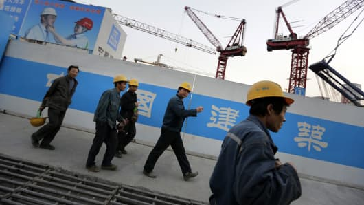 Workers walk outside a construction site in Beijing's central business district.
