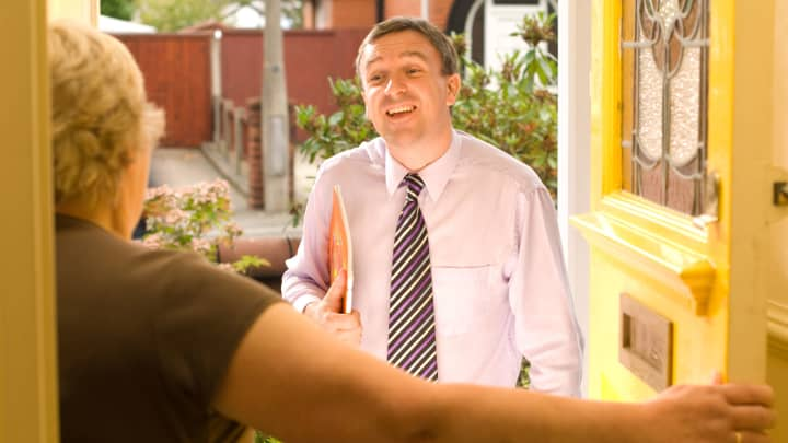 Image result for a salesman talking to a woman at her home door