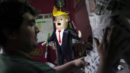 Mexican artisan Dalton Ramirez works on a pinata as another depicting U.S. Republican presidential candidate Donald Trump is seen at his workshop in Reynosa, Mexico, June 23, 2015.