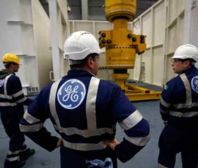Employees Stand As A Subsea Oil And Gas Tree Is Maneuvered By A Crane At The