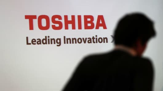 A man walks past the logo of Toshiba displayed at the company's headquarters in Tokyo on February 14, 2017.