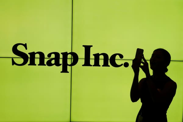 A woman stands in front of the logo of Snap Inc. on the floor of the New York Stock Exchange (NYSE) while waiting for Snap Inc. to post their IPO, in New York City.
