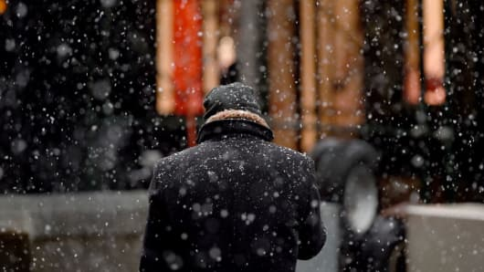 A man checks his phone as snow fall outside the New York Stock Exchange on Wall Street in New York March 10, 2017 .