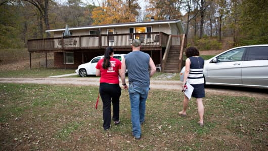 A realtor, right, walks with potential home buyers as they tour the property of a home for sale in Sparland, Illinois.
