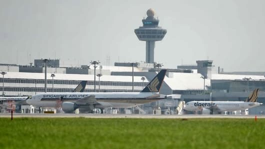 A Singapore Airlines and a Tiger Air plane parked at Changi International Airport in Singapore on July 29, 2014.
