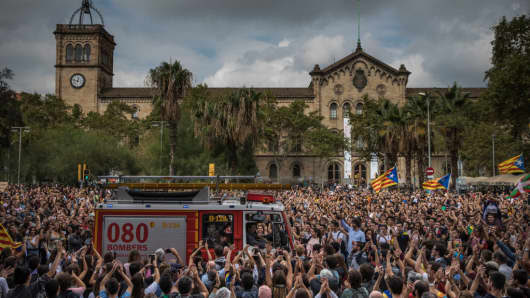 Students cheer fire officers as they drive through the crowd during a protest against the violence that marred yesterday's referendum vote outside the University on October 2, 2017 in Barcelona, Spain. Catalonia's government met Monday to discuss plans to declare independence after the results of yesterday's disputed referendum.