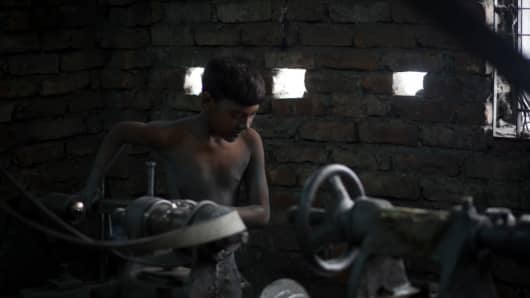 A child working in an aluminium pot making factory, reportedly under coercion, on May 23, 2017 in Dhaka, Bangladesh.