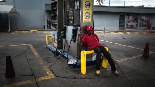 An attendant sits at a closed Petroleos de Venezuela SA (PDVSA) gas station in Caracas, Venezuela, on Friday, Sept. 22, 2017.