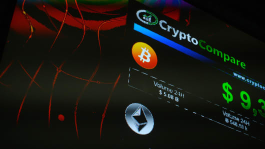 The symbols of Bitcoin and Ethereum cryptocurrencies sit displayed on a screen during the Crypto Investor Show.