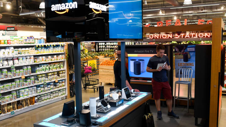 Retail consultant Matt Bailey (left) helps customer Geoff Witherspoon at the Amazon Pop-Up in the Union Station Whole Foods on Thursday, March 22, 2018.