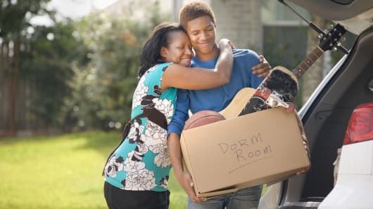 Mother hugging teenage son as he packs for college