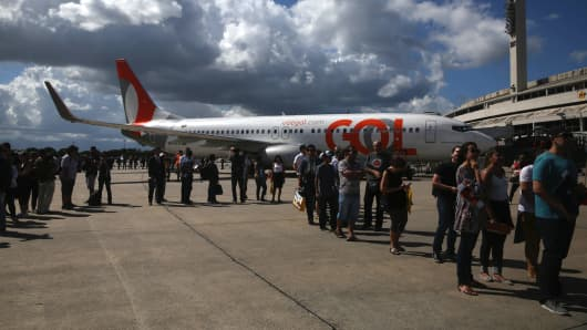 Attendees stand in line in front of a Boeing Co. aircraft operated by GOL Airlines SA during the International Brazil Air Show (IBAS) at Rio Galeao International Airport in Rio de Janeiro, Brazil, on Saturday, April 1, 2017.