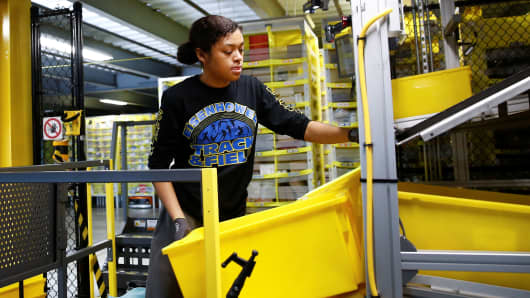 An employee is working on order picking from Amazon Fulfillment Center inventory in Kent, Washington, October 24, 2018.