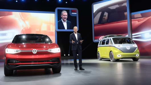 Herbert Diess, head of the Volkswagen AG (VW) brand, speaks while flanked by a VW I.D. Crozz concept electric automobile, left, and an I.D. Buzz camper van during the first media preview day of the IAA Frankfurt Motor Show in Frankfurt, Germany, on Tuesday, Sept. 12, 2017.