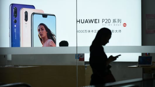 A Huawei poster is displayed in a store in Beijing on August 7, 2018.