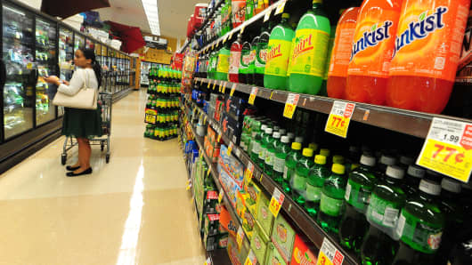 A woman shops for frozen foods on an aisle across from sodas and other sugary drinks at a superrmarket in Monterey Park, California.