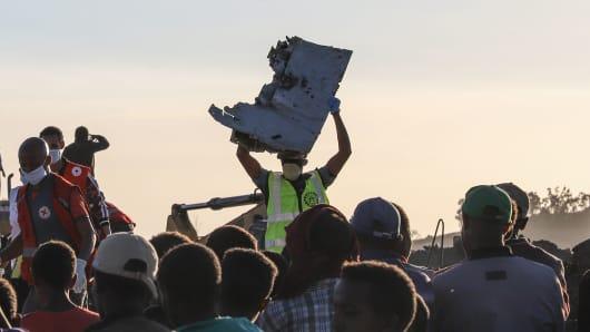 Un hombre lleva un pedazo de escombros sobre su cabeza en el lugar del accidente de un vuelo de Ethiopian Airlines con destino a Nairobi cerca de Bishoftu, una ciudad a unos 60 kilómetros al sureste de Addis Abeba, Etiopía, el 10 de marzo de 2019.