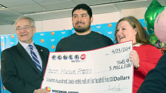 Powerball winner Manuel Franco (Center) accepts his jackpot prize from Wisconsin Department of Revenue Secretary Peter Barca (L) and Wisconsin Lottery Director Cindy Polzin (R).